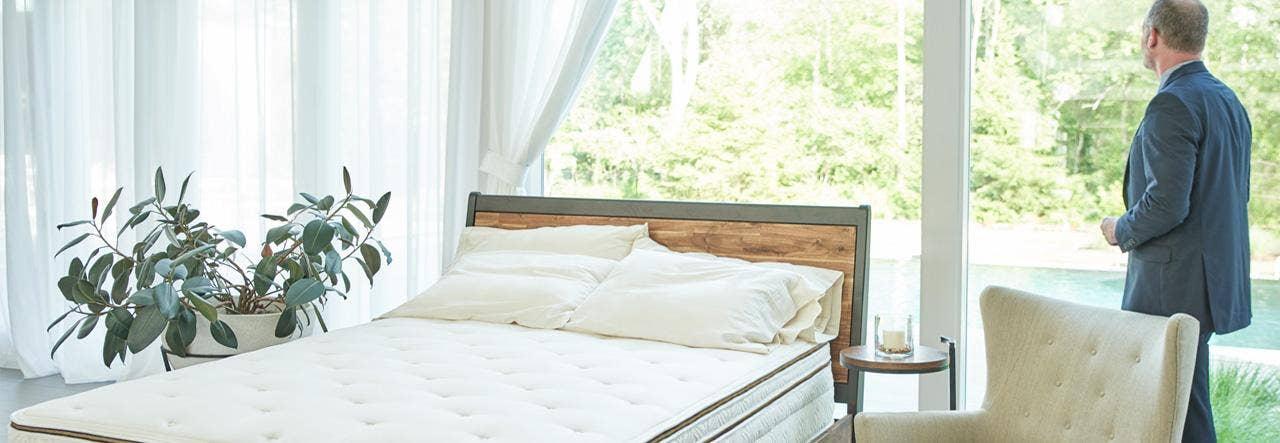 man standing at bedroom window with naturepedic halcyon arcadia organic mattress