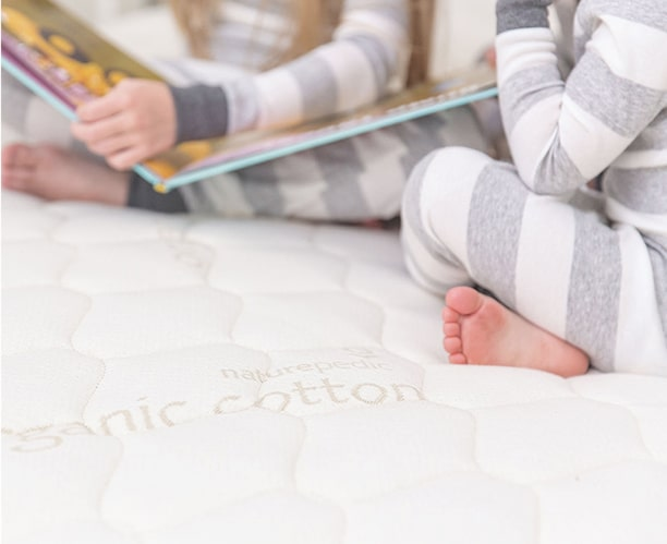 Two kids sitting on bed reading book