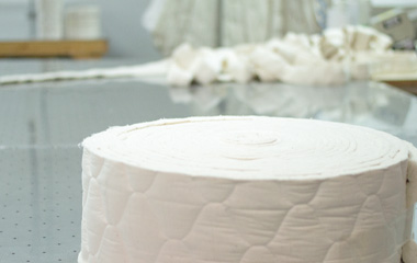 Roll of quilted organic cotton fabric and fill on table