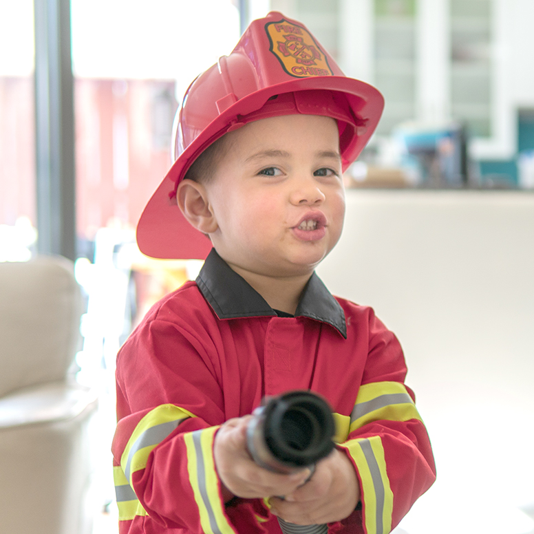 Boy dressed in fireman's costume holding up water hose pretending to spray