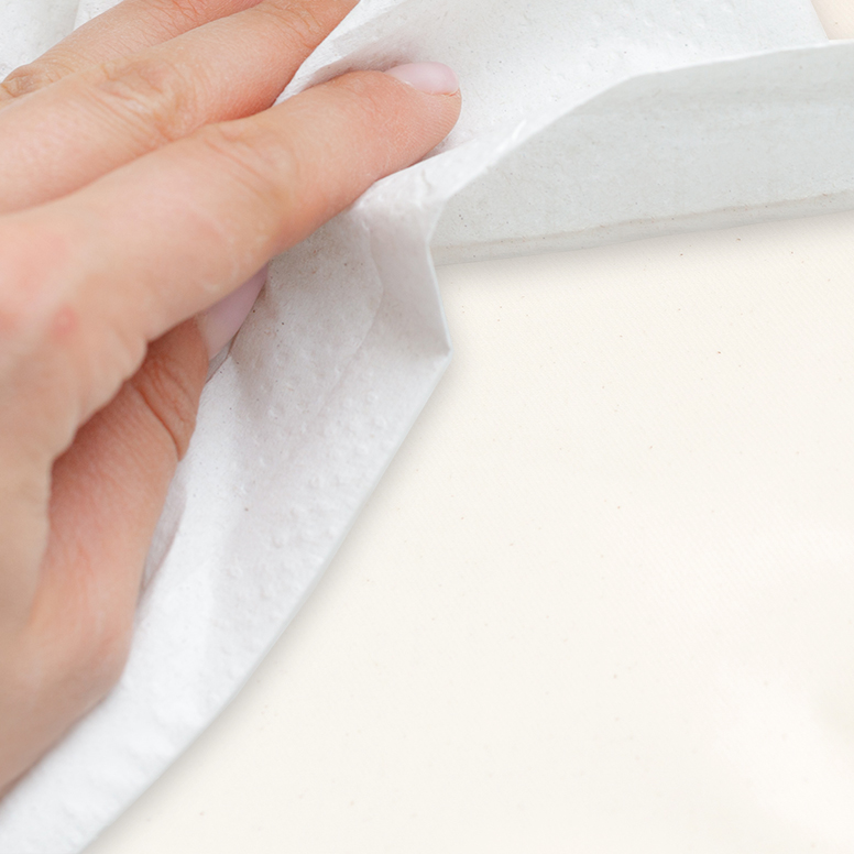 Close-up of wiping mattress surface clean with paper towel