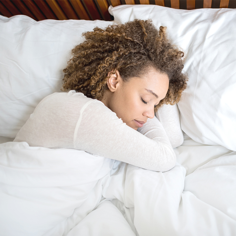 Close-up of woman sleeping in bed snuggling blanket