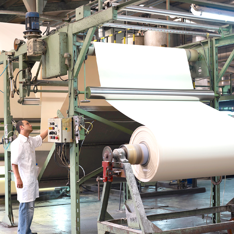Worker in factory operating fabric processing equipment