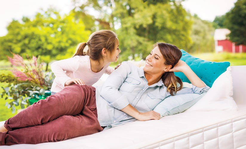 Angled shot of mom and daughter smiling at each other on mattress in outdoor setting