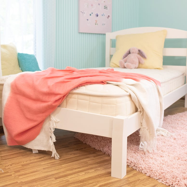 Twin mattress in kids room with blanket hanging over