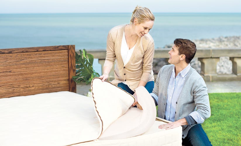 Happy couple holding quilted top and latex insert with mattress encasement unzipped in outdoor setting