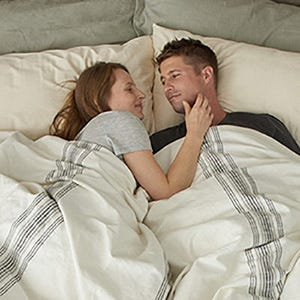 couple in bed laying on naturepedic organic pillows