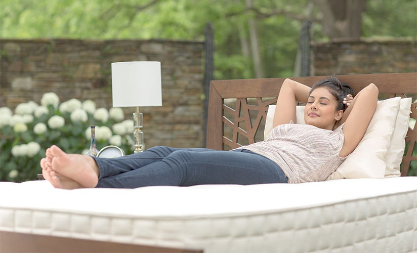 Angled shot of woman laying on back sleeping on mattress in outdoor setting