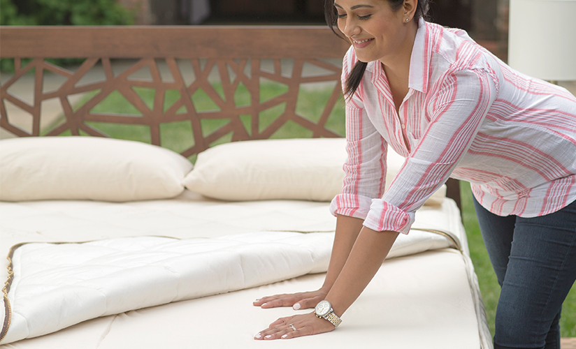 Woman feeling latex insert in mattress with encasement quilt top pulled back